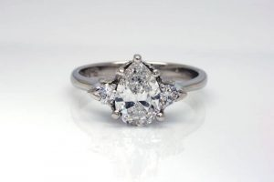 Image of a 1.0 carat pear-shaped Argyle white diamond engagement ring, flanked by two 2.5mm round Argyle diamonds all set in a recycled platinum band