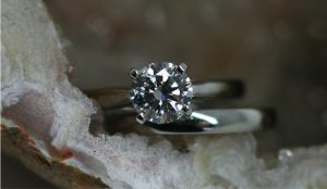 Image of a lab-grown, solitaire diamond ring in recycled platinum with its matching wedding ring