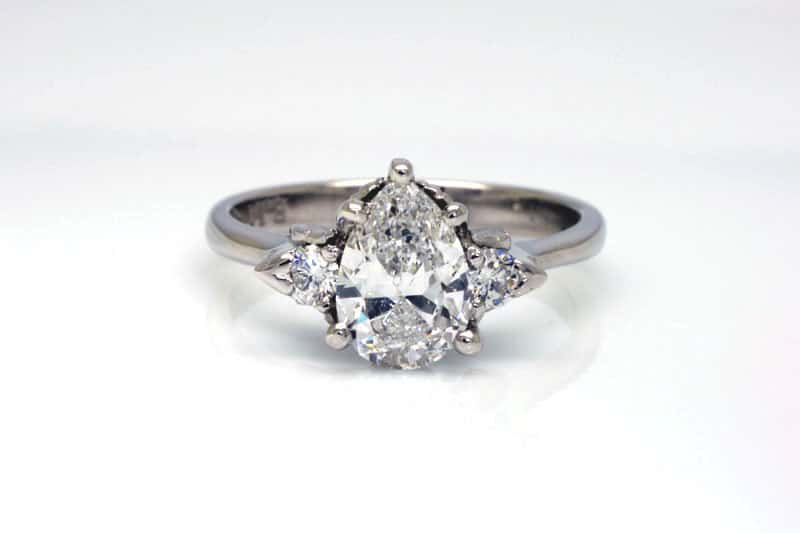 1.0 carat pear-shaped Argyle white diamond engagement ring, flanked by two 2.5mm round Argyle diamonds all set in a recycled platinum band