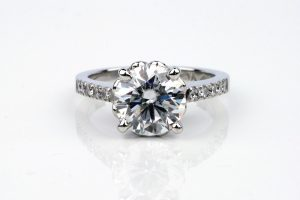 4-claw Moissanite engagement ring featuring a 9mm centre stone with natural accent diamonds in the shoulders. The ring is made with recycled platinum