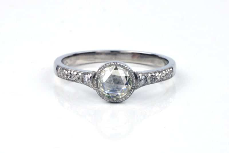 This recycled platinum engagement ring features and bezel set vintage rose cut diamond in a milgrain setting. The ring's shoulders are engraved and are set with two more small, round vintage diamonds.