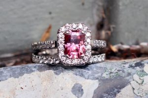 Halo style engagement ring featuring Argyle diamonds in the halo and a bright pink, emerald cut moissanite as the hero gem, pictured with its matching eternity style wedding band. Both rings were made usng recycled platinum - by Ethical Jewellery Australia