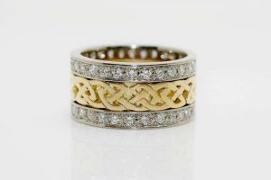 Stunning 3 band wedding ring featuring two Argyle diamond set eternity-style bands in 18 carat recycled white gold either side of a 18 carat recycled yellow gold band pierced in a Celtic knot pattern.
