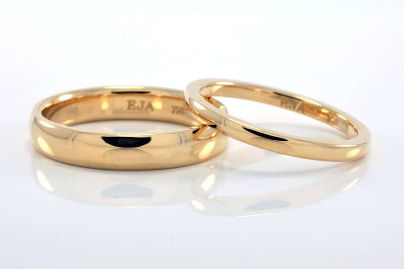 Matching pair of his and hers wedding rings in 18 carat recycled gold in a simple half-round profile with a polished finish.