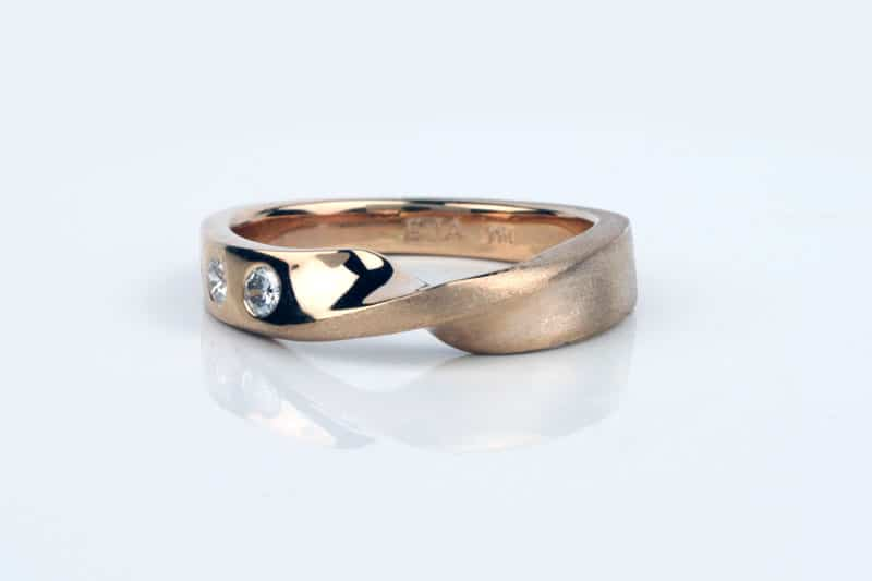 18 carat recycled rose gold wedding ring with a Mobius twist, set with recycled diamonds and finished half polished and half wire-brushed.