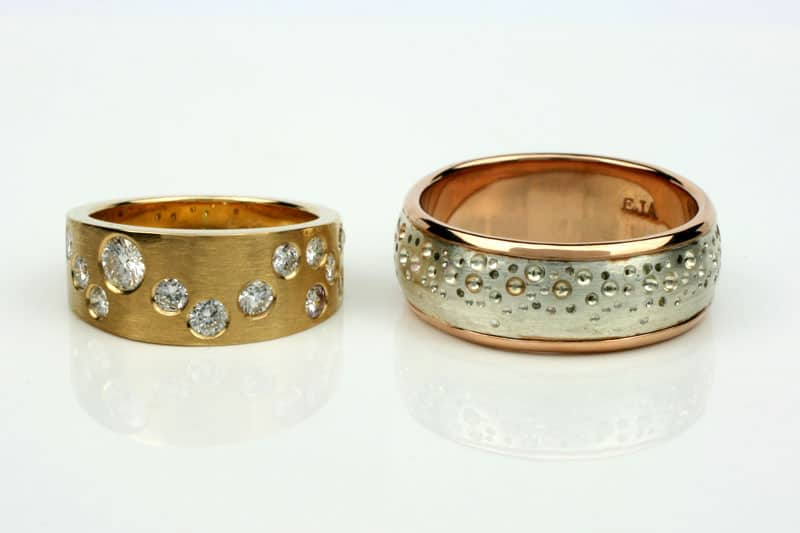 Pair of wedding bands - hers a tapered 18 carat gold band with recycled diamonds in a Gemini constellation patter, and for him (a keen surfer) recycled 18 carat rose gold with a recycled silver sleeve embossed with a bubble pattern