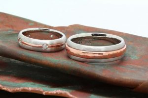 Matching pair of wire-brush finished, platinum wedding rings with a band of recycled copper around the middle of each ring. Hers also features six hammer set Argyle diamonds evenly spaced around the ring.