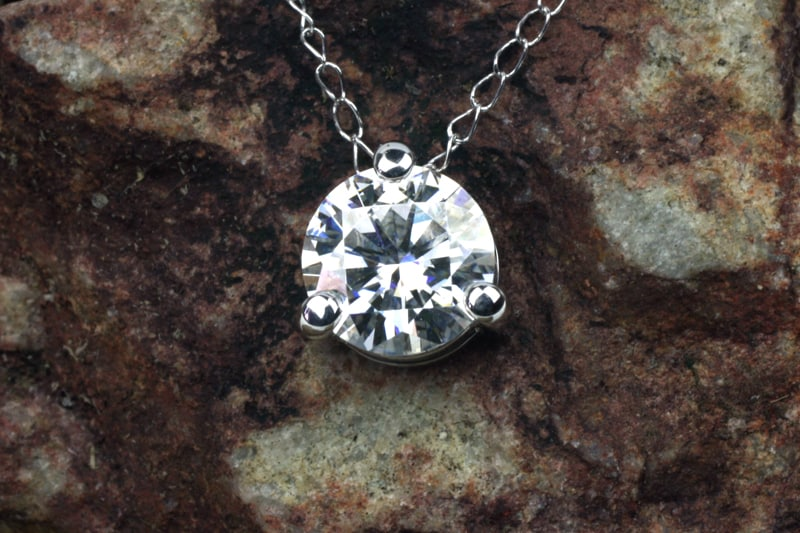 Moissanite pendant in a simple platinum three claw basket setting